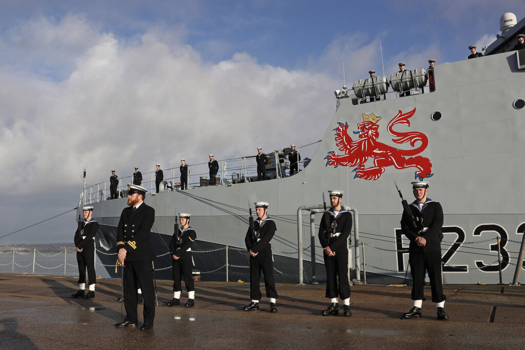under tamars giant lion motif the guard of honour stands at ease on a wet jetty - naval post- naval news and information