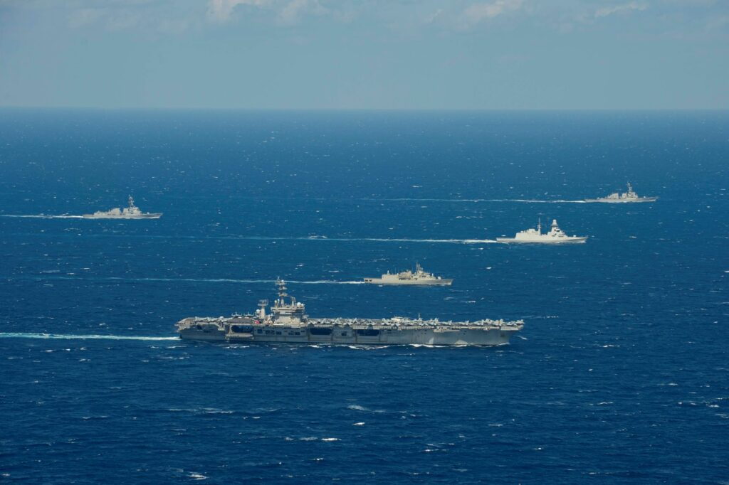 the hellenic hydra-class frigate psara (f 454), center front, and the italian carlo bergamini-class frigate virginio fasan (f 591), center, sail in formation with ships assigned to the ike carrier strike group in the mediterranean sea, march 11, 2021.