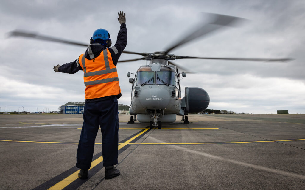 leading seaman paul rendle signals to the first crowsnest helicopter to take off - naval post- naval news and information