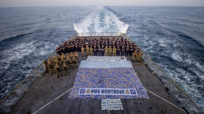 Royal Navy and Royal Marines personnel from HMS Montrose stand with more than 6,200 lbs of narcotics seized from a vessel in the Arabian Sea, March 12, 2021 (Photo: AET Josh Edwards RN)