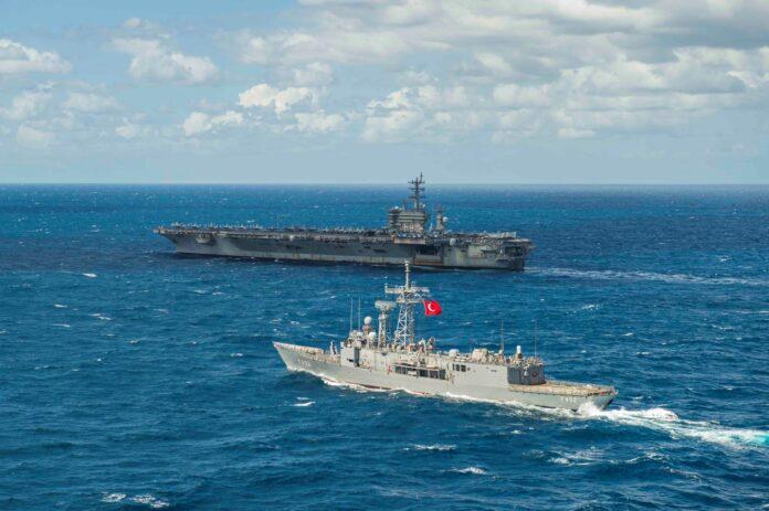 The Turkish frigate TCG Gemlik (F 492), front, sails alongside the Nimitz-class aircraft carrier USS Dwight D. Eisenhower (CVN 69), in the Mediterranean Sea, March 17, 2021.