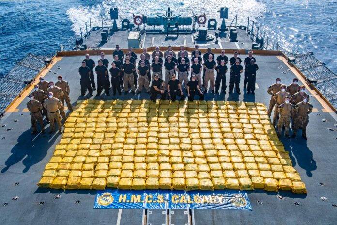 Members of HMCS CALGARY stand with contraband seized during counter-smuggling operations on 17 May, 2021 in the Arabian Sea during OPERATION ARTEMIS and as part of Combined Task Force 150.