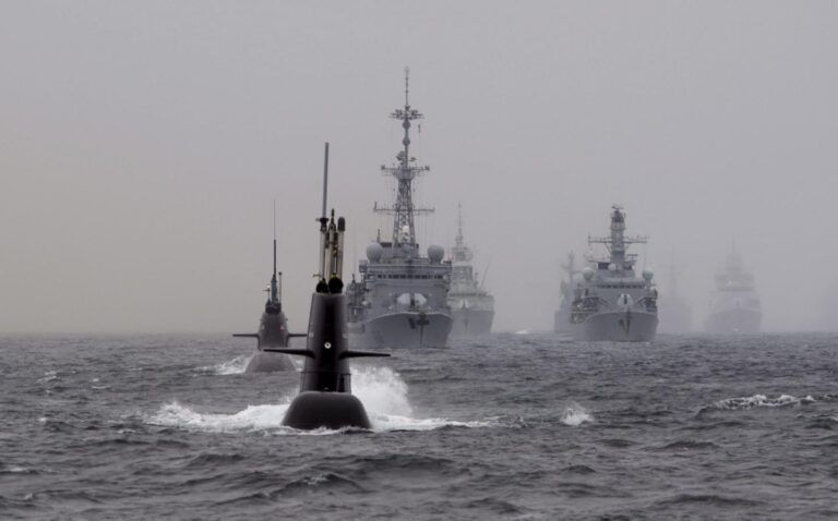Why are warships universally gray? Why are submarines painted black?
