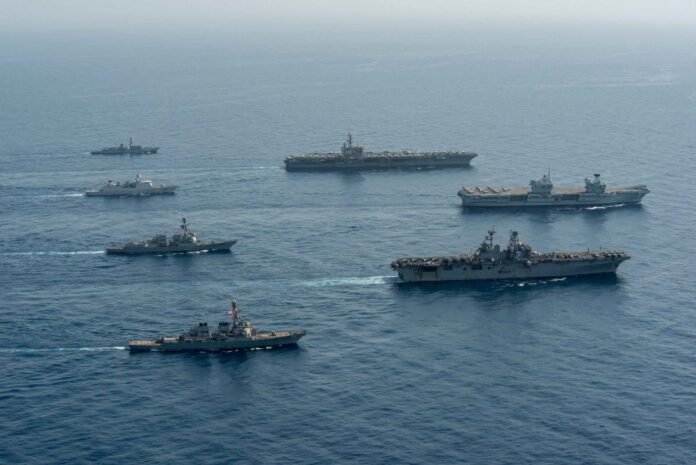 Ships of the UK Carrier Strike Group, USS Ronald Reagan Carrier Strike Group, and Iwo Jima Amphibious Ready Group operate in formation in the Gulf of Aden, July 12, 2021.
